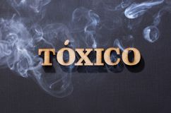 Toxic word in wooden letters with smoke. Tóxico. Toxic word in wooden letters with smoke stock image