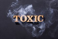 Toxic word in wooden letters with smoke. Tóxico. Toxic word in wooden letters with smoke royalty free stock photos