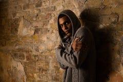 Toxicomane posant près du mur de briques photo stock