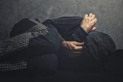 Toxicomane s'étendant sur le plancher dans l'agonie Photo stock