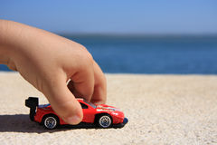 Toy. Close-up of a child hand playing with a red car royalty free stock photos
