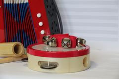 Toy Accordion and Percussion Set on Sheet Music Background royalty free stock photo