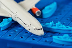 Toy airliner crashed among toy warships. Toy airliner crashed into the sea among toy warships Stock Images