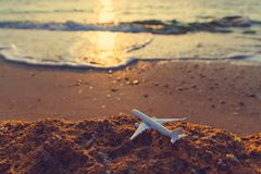 Toy airplane on the beach at sunset. Travel and air transportation concept stock photo