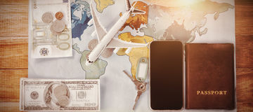 Toy airplane with currency and passport by smartphone on map at table. Directly above shot of toy airplane with currency and passport by smartphone on map at Royalty Free Stock Image