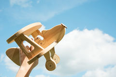 Toy airplane in hand and blue cloudy sky as background. Stock Image