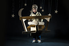 Toy airplane at night. Boy is playing with handmade toy plane. Decorations of night sky is on background Stock Images