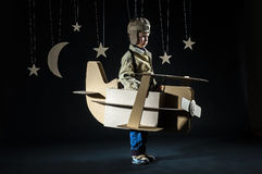 Toy airplane at night. Young pilot is flying on cardboard airplane at night. Side view Stock Photography