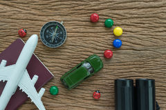 Toy airplane, passport, compass, binoculars and miniature car on Royalty Free Stock Photography