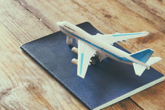 Toy airplane and passport over wooden table. faded style image.  royalty free stock photo