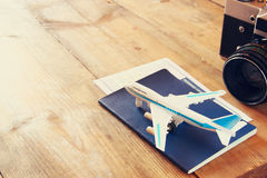 Toy airplane and passport over wooden table. retro style image stock image