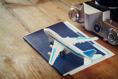 Toy airplane and passport over wooden table. retro style image.  royalty free stock photo