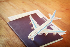 Toy airplane and passport over wooden table. retro style image stock photos
