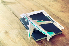 Toy airplane and passport over wooden table. retro style image.  stock photography
