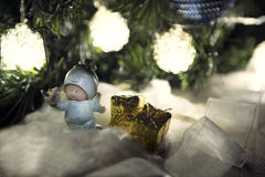 Toy angel with presents. Christmas background: little angel with presents under Christmas tree Stock Photo