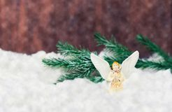 Toy angel with wings on white snow. Holiday toy angel with wings on white snow near Christmas tree branches on wooden background for new year Royalty Free Stock Images