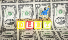 Toy atempts to climb out of debt Stock Photo