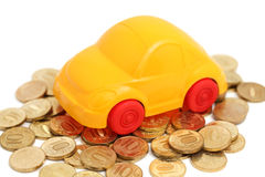 Toy auto stand on pile of coins (isolated) Stock Image