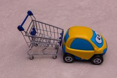 Toy automobile beside Shopping trolley on concrete background royalty free stock photos