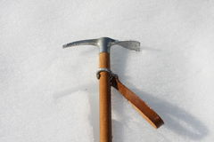 Toy axe in the cold snow in the mountain Stock Photos