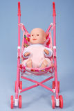 Toy baby buggy on blue background. Stock Image