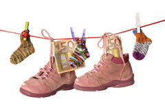 Toy and baby shoes hanging on a cord. isolated on Royalty Free Stock Photos