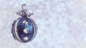 Toy ball decoration on a Christmas tree in blue. On a bright bokeh background on a New Year and Christmas holiday Royalty Free Stock Images