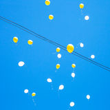 Toy balloons float in blue sky Stock Image