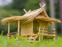 Toy bamboo hut on green grass Stock Photo