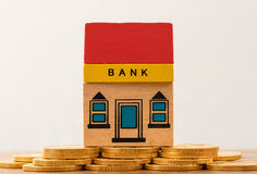 Toy bank building on gold coin assets stock photography