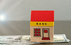 Toy bank building on US dollar assets Royalty Free Stock Photo