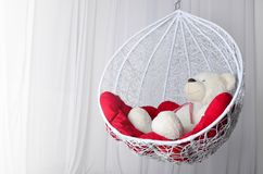 Toy bear and decorative swing with red pillows. cozy place to relax stock images