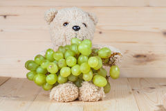 Toy bear and grapes on plate Stock Photos