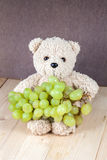 Toy bear and grapes on plate Royalty Free Stock Image