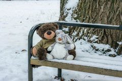 Toy bear and a hare sitting on the bench in winter Stock Image