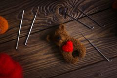 Toy bear with heart of wool and tools for felting royalty free stock image