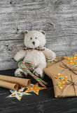 Toy bear, homemade Christmas gifts in Kraft paper, candy n wooden surfaces. Royalty Free Stock Images