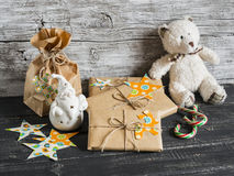 Toy bear, homemade Christmas gifts in Kraft paper, candy on a wooden surfaces. Stock Photos