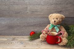 Toy bear with mug of sweets and Christmas decorations on wooden Royalty Free Stock Images