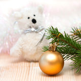 Toy bear and an orange ball on the Christmas tree Stock Image