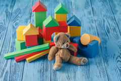 Toy bear and pile wooden building blocks Stock Image