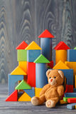 Toy bear and pile wooden building blocks stock photography