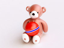 Toy bear With Red Ball On Knees Royalty Free Stock Images