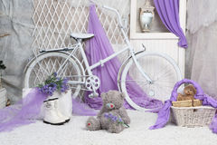 A toy bear sits on carpeting in a bright room. With lilac curtains stock photos