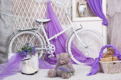 A toy bear sits on carpeting in a bright room. With lilac curtains stock images