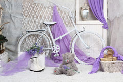 A toy bear sits on carpeting in a bright room. With lilac curtains royalty free stock image