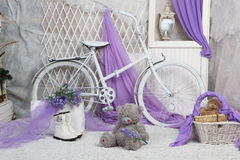 A toy bear sits on carpeting in a bright room. With lilac curtains royalty free stock photography