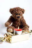 Toy bear Teddy and burning candle. Royalty Free Stock Images