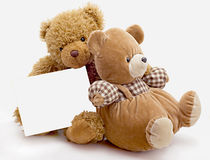 Toy bears. Two toy bears and empty card isolated on the white royalty free stock image