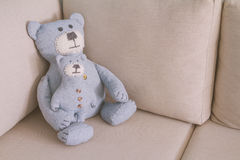 Toy bears sitting on a sofa. Toy bears -father and son- sitting on a sofa, toned Stock Image